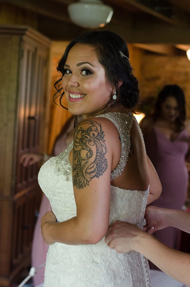 a smiling bride looking over her shoulder while a bridesmaid buttons the back of her dress