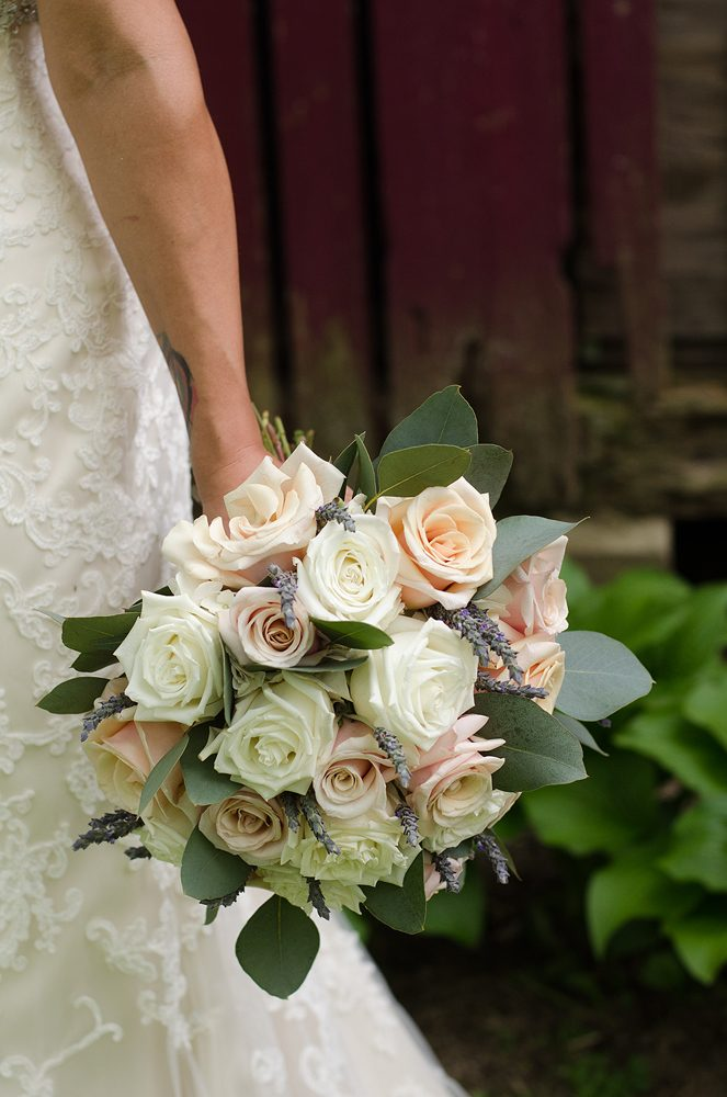 close up of a bride holding her bouquet by her side with peach and white roses