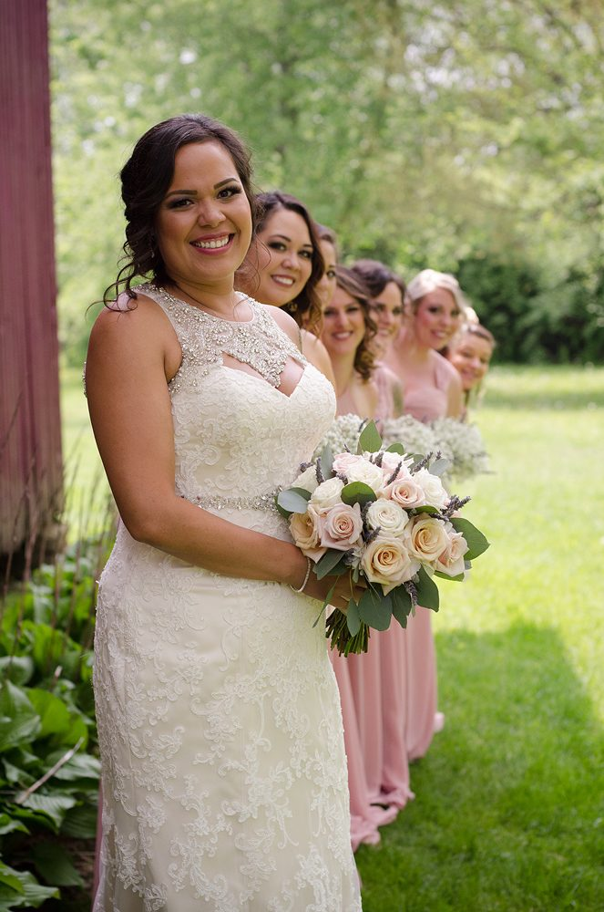 a smiling bride in front of her line of bridesmaids