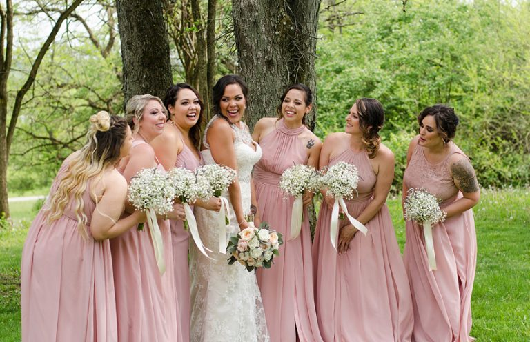 bride and bridesmaids laughing while posing in front of a row of trees