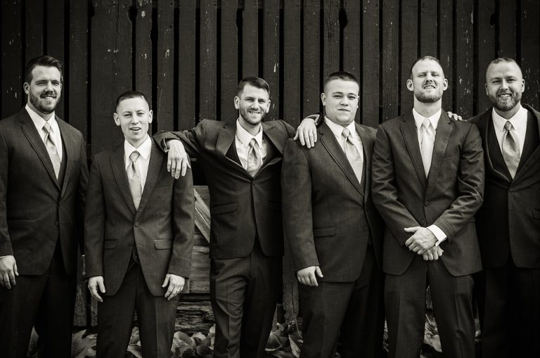 black and white photo of a groom and groomsmen posing and leaning on each other in front of a barn