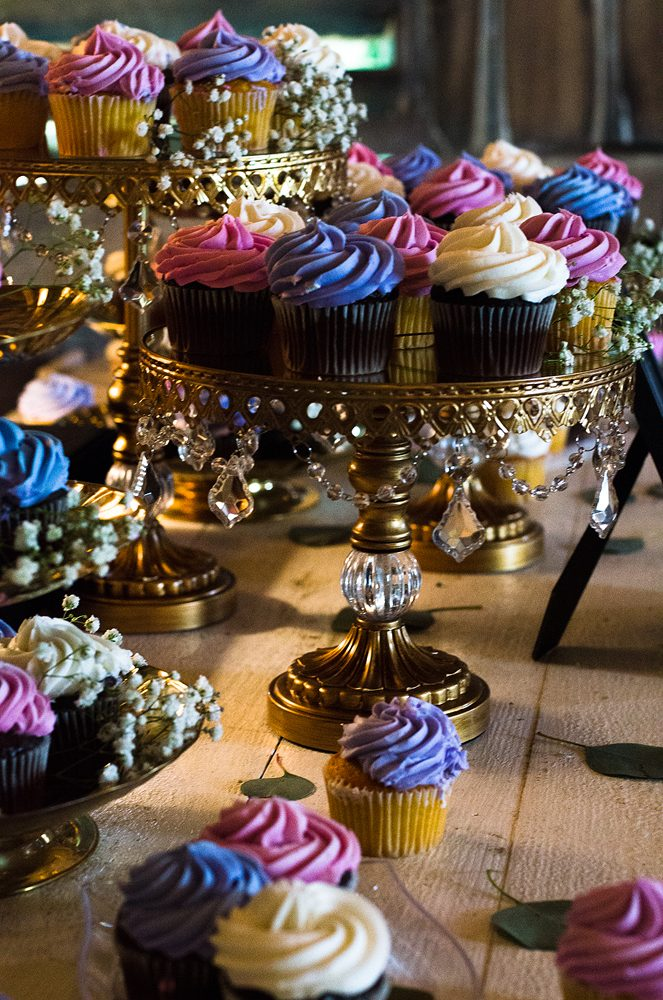 close up of wedding cupcakes on an elaborate cake plate with blue, purple and white cupcakes