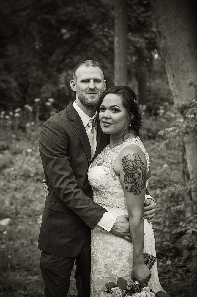 black and white photo of a bride and groom in the forest