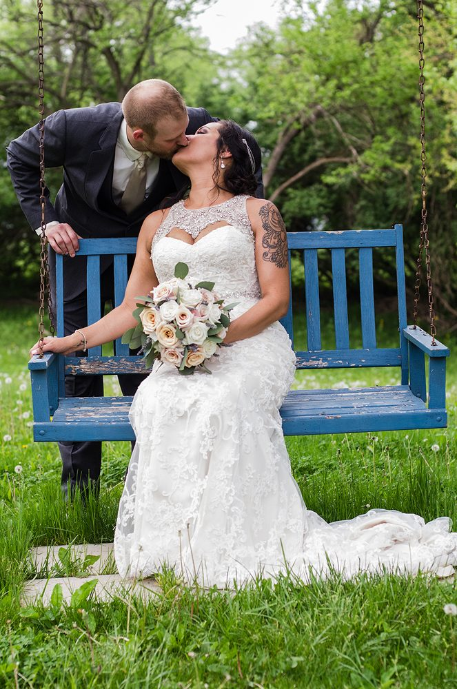groom leaning over and kissing his bride while she sits on a blue wooden swing