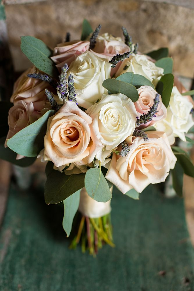 close up of a bridal bouquet on a green chair with peach and white colored roses