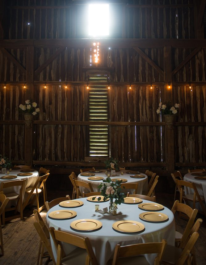a table setting in a barn for a wedding reception with gold chargers, greenery and soft window light streaming in from a window