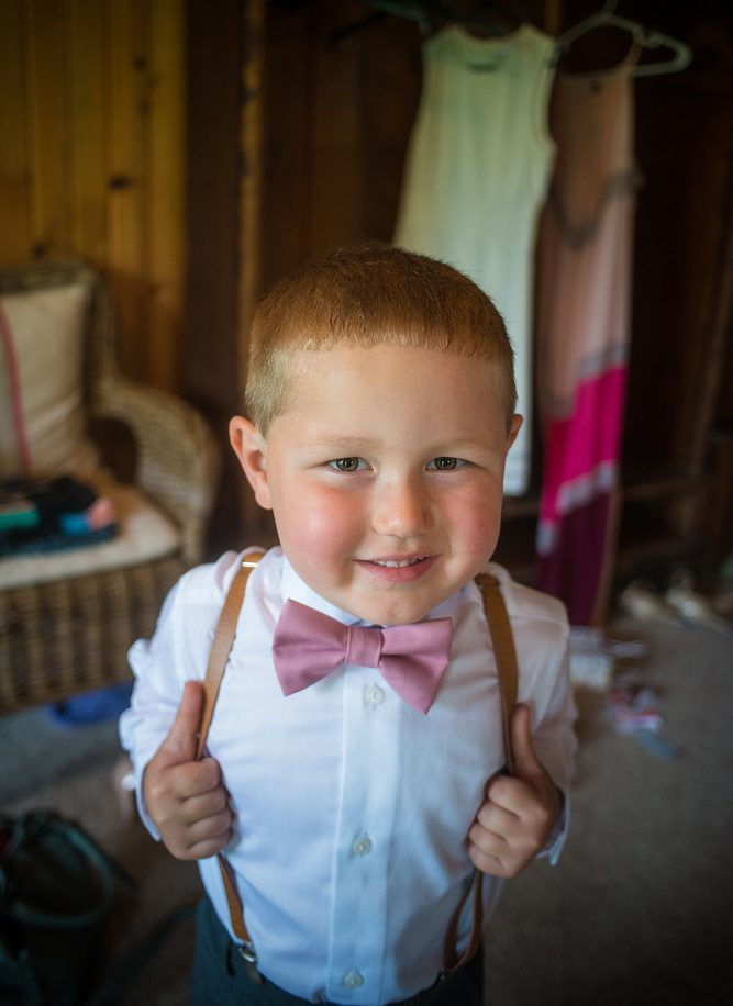 small boy dressed in suspenders as a ring bearer smiling at the camera