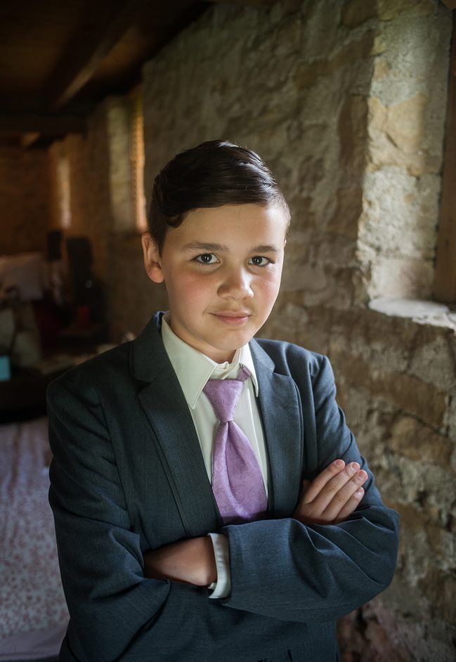 young boy dressed up as a ring bearer posing in soft window light