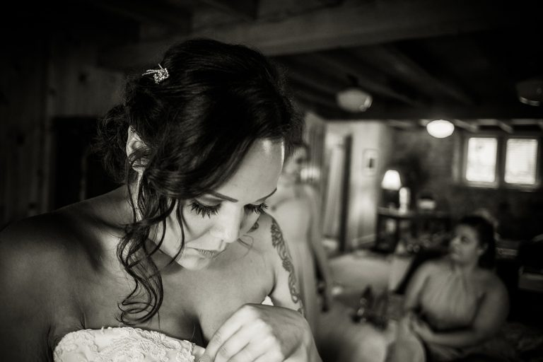 black and white photo of a bride getting dressed