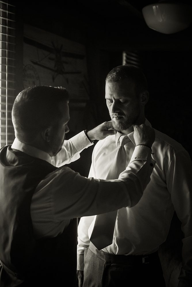 black and white photo of groomsman helping the groom put his tie on