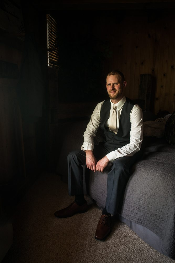 groom posing in dramatic natural window light on the side of a bed