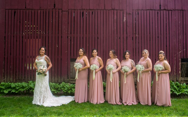 bride and bridesmaids posing in front of a red barn