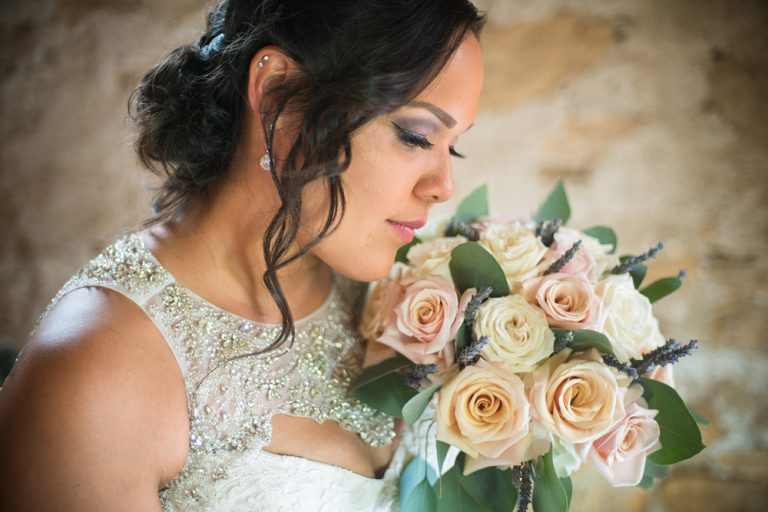 close up of a bride with her eys closed holding her bouquet close to her face
