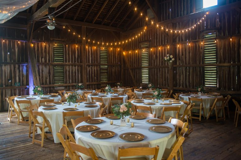 barn reception tables set with gold chargers and greenery and strings of lights