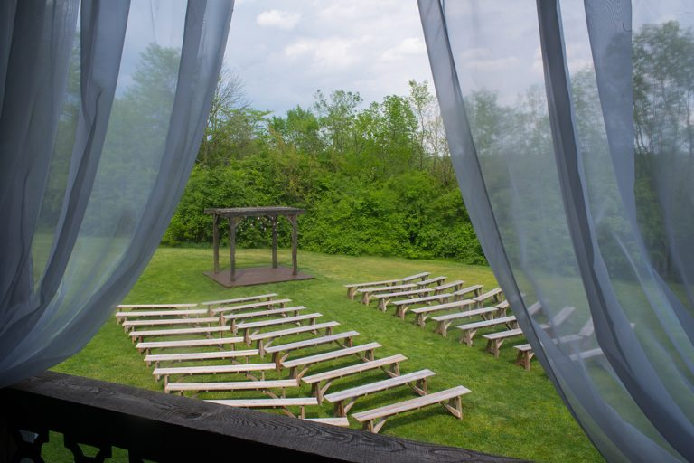a view through the barn window looking down onto wood benches at the ceremony location