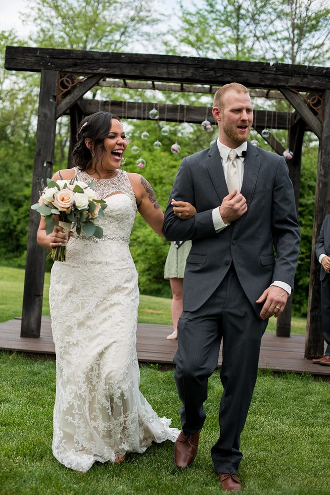 bride and groom walking down the aisle laughing during recessional