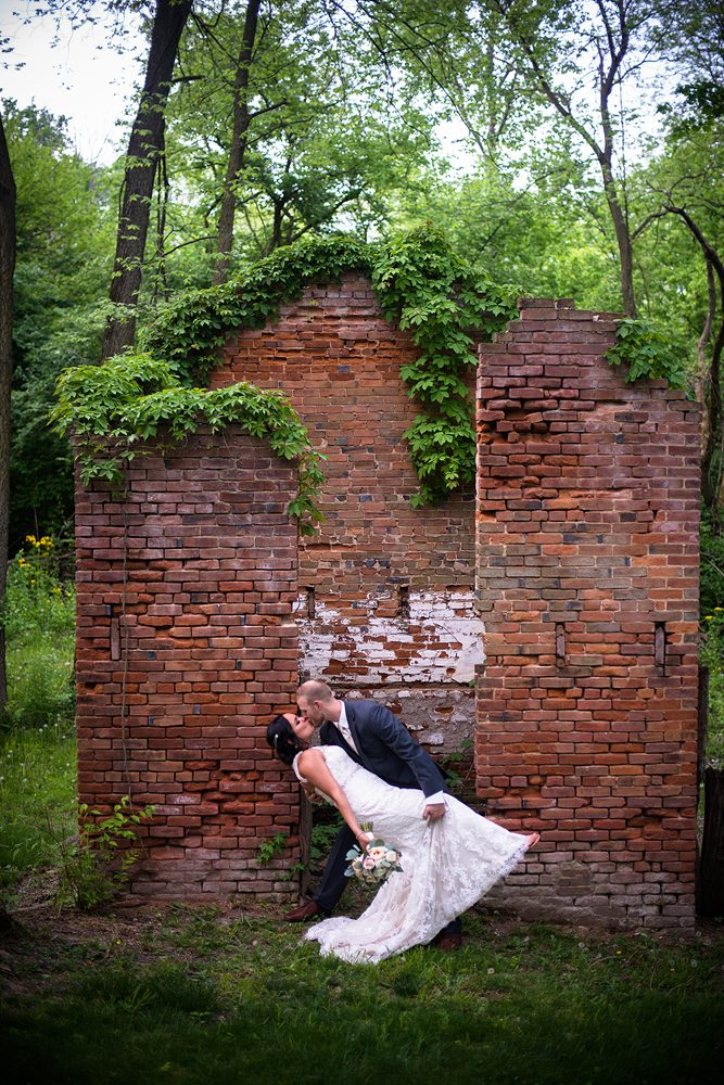 groom dipping and kissing his bride in front of a run down red brick building