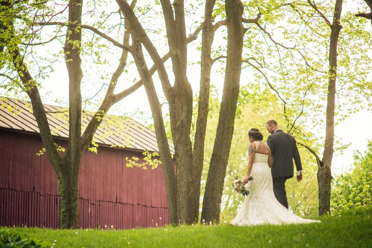 bride and groom walking at sunset in front of a red barn