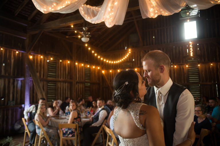 bride and groom's first dance in a barn wedding reception