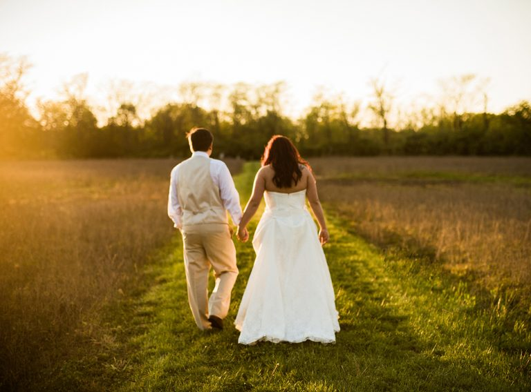 bride and groom walking into the sunset at Canyon Run Ranch in Pleasant Hill Ohio