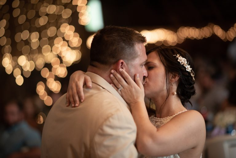 romantic first dance of bride and groom with warm yellow bokeh from lights at Lost Creek Memory Barn in Casstown, Ohio