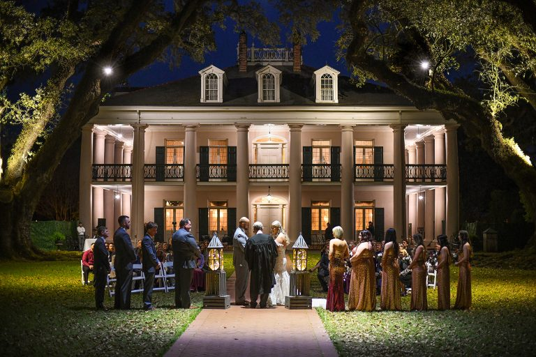 nightime photo of a wedding ceremony with the mansion and live oaks at Oak Alley in Vacherie Louisiana