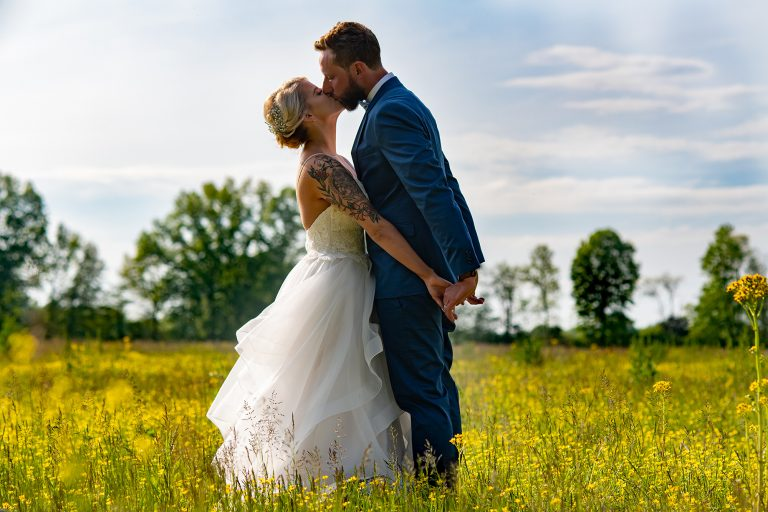 bride and groom kissing in a field of yellow wild flowers