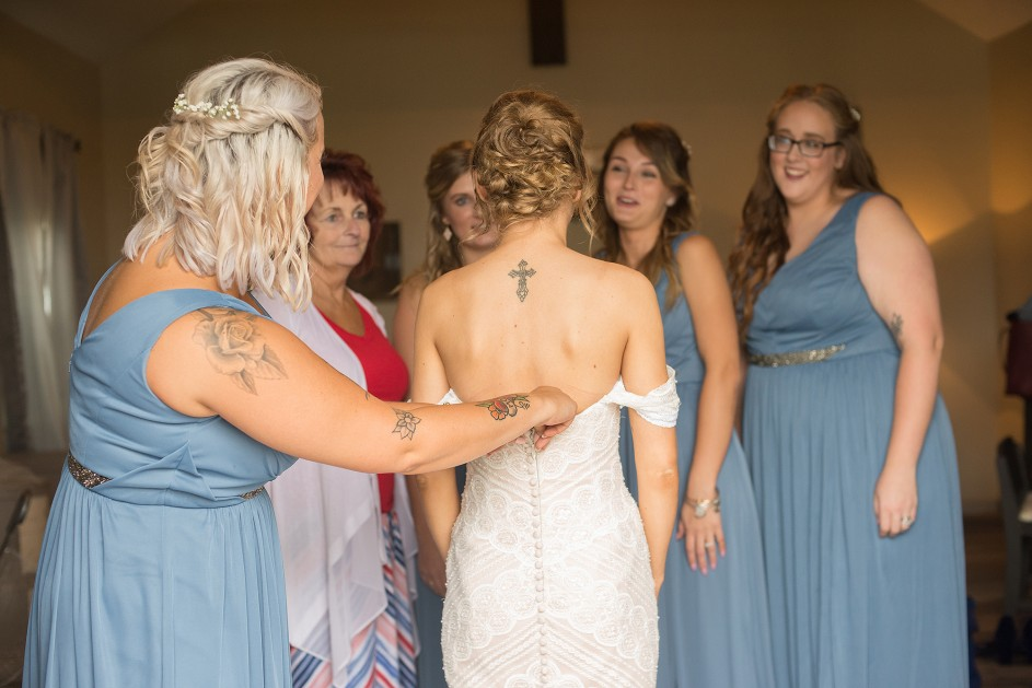light and airy photo of tatooed bride having her dressed zipped up by bridesmaids in blue dresses
