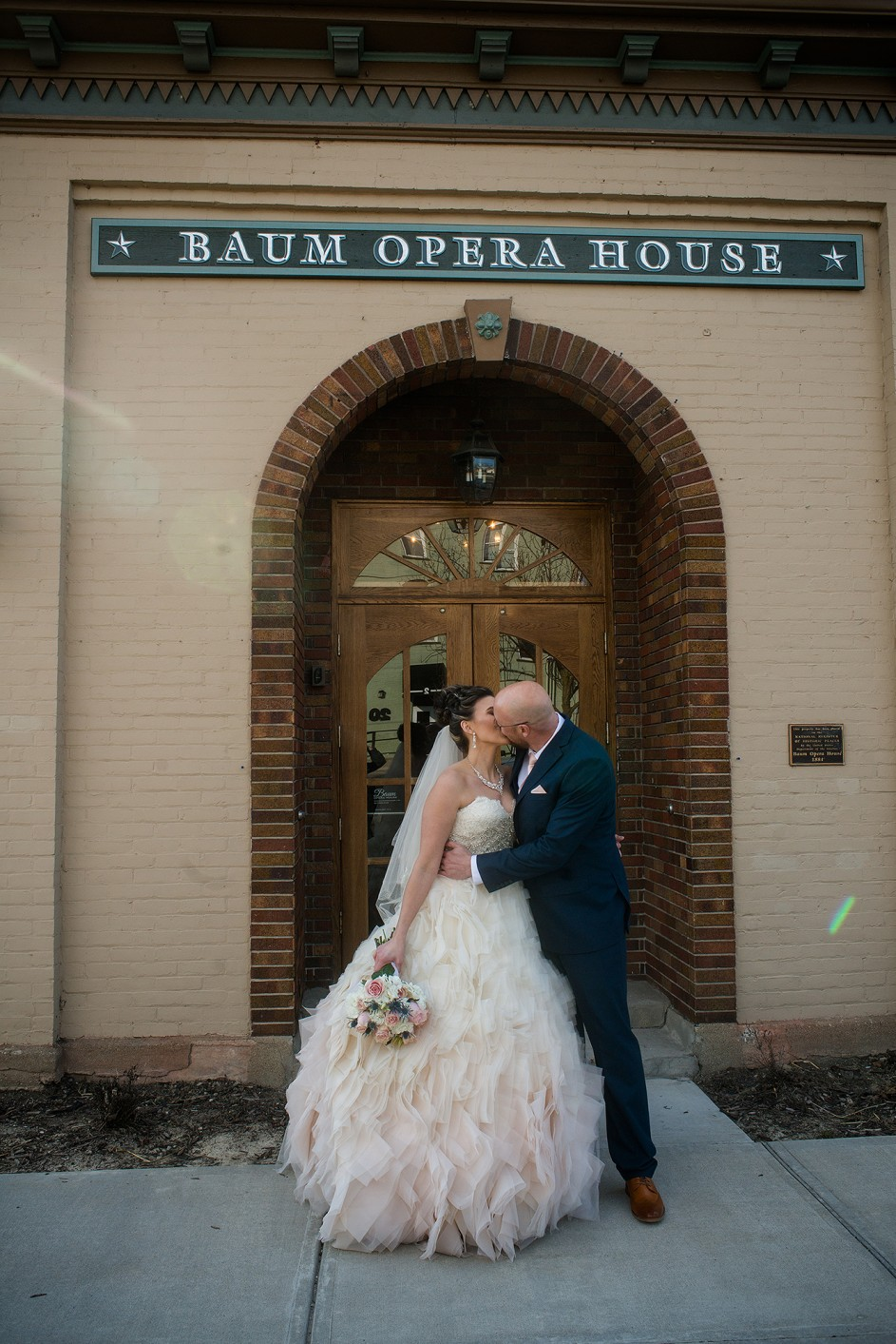 bride and groom kissing in front of the Baum Opera House Miamisburg Ohio