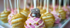 close up of wedding rings on pink and gold cake pops at Cooper Creek Event Center in Blue Ash, Ohio